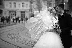 Pares felices de los valentynes del recién casado que presentan y que se besan en eu viejo Foto de archivo