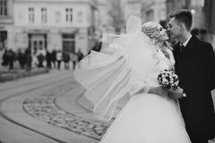 Pares felices de los valentynes del recién casado que presentan y que se besan en eu viejo Imágenes de archivo libres de regalías