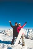 Pares felices de snowboarders en las montañas alpinas Fotografía de archivo libre de regalías