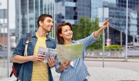 Pares felices de turistas con la gu?a y el mapa de la ciudad fotografía de archivo