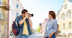 Pares felices de turistas con las mochilas y la c?mara fotos de archivo libres de regalías