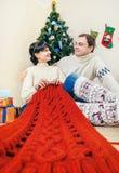 Pares felices debajo del árbol de navidad con el trabajo que hace punto Fotos de archivo