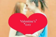 Pares felices del día de tarjetas del día de San Valentín que llevan a cabo símbolo rojo del corazón Fotos de archivo libres de regalías