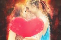 Pares felices del día de tarjetas del día de San Valentín que llevan a cabo símbolo rojo del corazón Fotografía de archivo libre de regalías