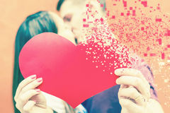 Pares felices del día de tarjetas del día de San Valentín que llevan a cabo símbolo rojo del corazón Imágenes de archivo libres de regalías