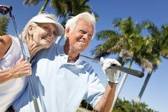Pares felices del hombre mayor y de la mujer que juegan a golf Imagen de archivo libre de regalías