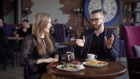 Pares felices del hombre y de la mujer que se sientan en cafetería en la tabla servida con la comida y las bebidas que pasan el t almacen de video