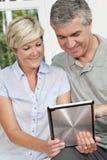 Pares felices del hombre y de la mujer usando el ordenador de la tablilla Fotos de archivo