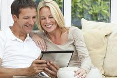 Pares felices del hombre y de la mujer usando el ordenador de la tablilla Imagenes de archivo