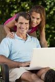 Pares felices del hombre y de la mujer usando el ordenador portátil Imágenes de archivo libres de regalías