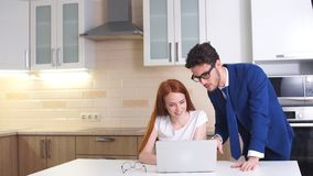 Pares felices del negocio que miran el ordenador portátil en casa en cocina
