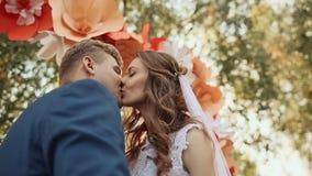 Pares felices del recién casado que se besan en el pasillo romántico de la boda con las decoraciones bajo la forma de flores Baja almacen de metraje de vídeo