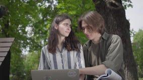Pares felices del retrato que pasan el tiempo junto en el parque, estudiando El var?n y los estudiantes en ropa casual almacen de video