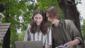 Pares felices del retrato que pasan el tiempo junto en el parque, estudiando El var?n y los estudiantes en ropa casual almacen de metraje de vídeo