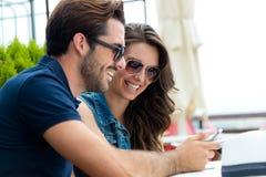 Pares felices del turista en ciudad usando el teléfono móvil Imagenes de archivo