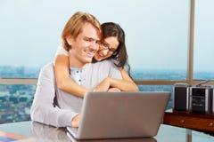 Pares felices delante de la computadora portátil Imagen de archivo
