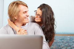 Pares felices delante de la computadora portátil Foto de archivo libre de regalías