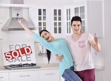 Pares felices delante de la muestra vendida de las propiedades inmobiliarias Imagen de archivo libre de regalías