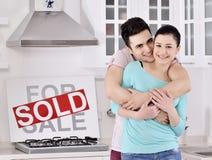 Pares felices delante de la muestra vendida de las propiedades inmobiliarias Imagen de archivo