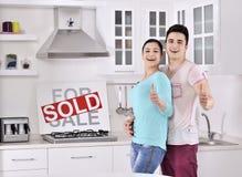 Pares felices delante de la muestra vendida de las propiedades inmobiliarias Imágenes de archivo libres de regalías