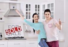 Pares felices delante de la muestra vendida de las propiedades inmobiliarias Foto de archivo libre de regalías
