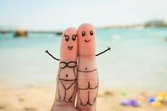 Pares felices El hombre y la mujer tienen un resto en la playa en bañadores Imagen de archivo