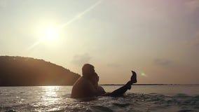 Pares felices el vacaciones en el mar Sirva los controles su muchacha y giro alrededor en el agua Mar que salpica sobre puesta de metrajes