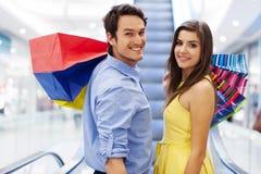 Pares felices en alameda de compras Foto de archivo libre de regalías