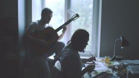 Pares felices en amor El retrato sensual imponente de la moda elegante joven se junta dentro Hombre joven que toca la guitarra pa metrajes
