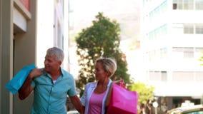 Pares felices en caminar hacia fuera que hace compras del día y llevar a cabo las manos metrajes