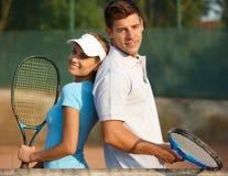 Pares felices en campo de tenis Foto de archivo libre de regalías