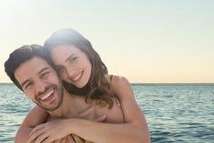 Pares felices en el abarcamiento de la playa Imagenes de archivo