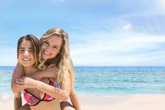 Pares felices en el abarcamiento de la playa Imágenes de archivo libres de regalías