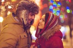 Pares felices en el amor al aire libre en luces de la Navidad de la tarde Fotos de archivo libres de regalías