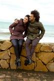 Pares felices en el amor que abraza delante del océano en invierno Fotos de archivo libres de regalías
