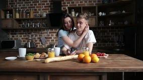 Pares felices en el amor que abraza en la cocina almacen de metraje de vídeo