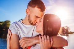 Pares felices en el amor que abraza y que se besa por el río en la puesta del sol Fotografía de archivo