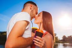 Pares felices en el amor que abraza y que se besa por el río en la puesta del sol Foto de archivo libre de regalías