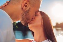 Pares felices en el amor que abraza y que se besa por el río en la puesta del sol primer Imágenes de archivo libres de regalías