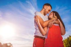 Pares felices en el amor que abraza y que sonríe contra el cielo azul en la puesta del sol Foto de archivo