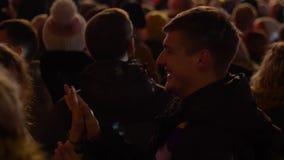 Pares felices en el amor que baila en la muchedumbre de gente en el fondo de proyectores en el concierto de la calle en la tarde almacen de metraje de vídeo