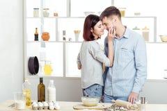 Pares felices en el amor que cocina la pasta y que se besa en cocina Imagen de archivo