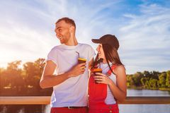 Pares felices en el amor que come café, abrazando y riendo en el puente de la puesta del sol Imágenes de archivo libres de regalías