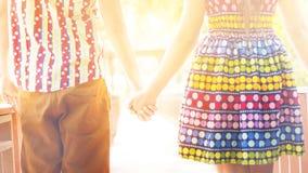 Pares felices en el amor que lleva a cabo las manos que caminan en el parque Fotos de archivo libres de regalías