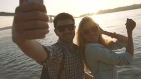 Pares felices en el amor que toma la foto del selfie cerca del río en una tarde maravillosa metrajes