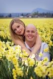 Pares felices en el campo de flores Fotos de archivo