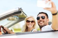 Pares felices en el coche que toma el selfie con smartphone imagen de archivo libre de regalías