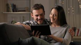 Pares felices en el contenido de la tableta de la ojeada de la noche almacen de video
