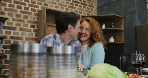 Pares felices en el hombre y la mujer de la cocina que abrazan mirando uno a que prepara la comida junta en casa almacen de video