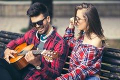 Pares felices en el parque que toca la guitarra Imagen de archivo